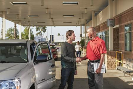 two men at a dealership shaking hands